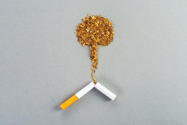 Zerbrochene tabakzigarette, tabak, der sich in form einer nuklearen explosion auf dem grauen tisch ausbreitet
