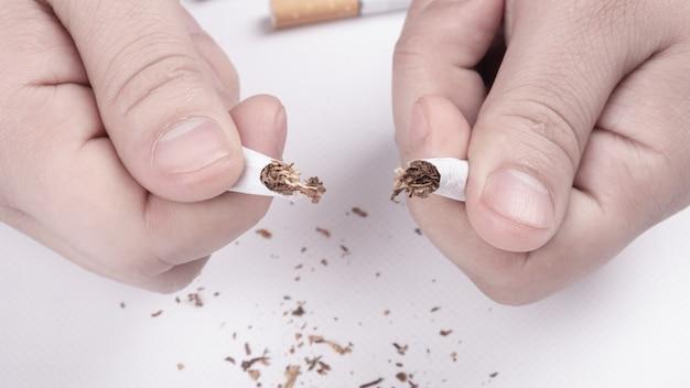 Zerbrochene zigarette in der hand nahaufnahme mit dem rauchen aufhören