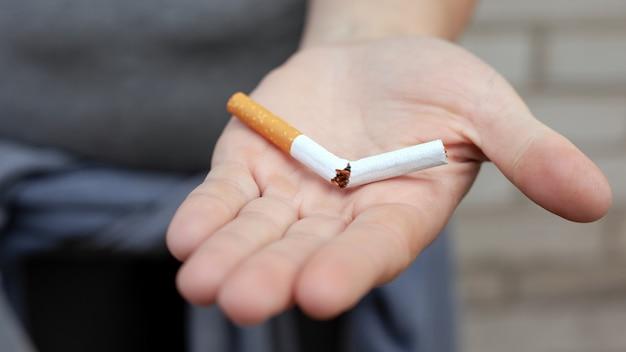 Zerbrochene zigarette in der hand, raucherentwöhnungskonzept, nikotinsucht.