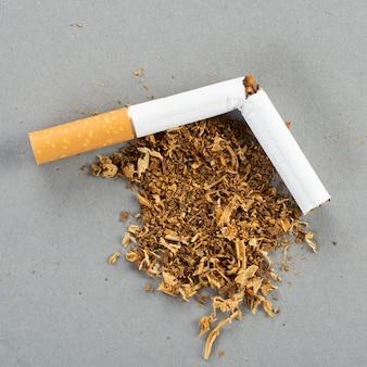 Zerbrochene zigarette mit tabak, tabak breitete sich auf dem grauen tisch aus