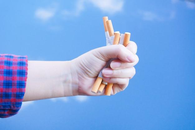 Zerbrochene zigarette zur hand. gewinnen mit süchtig machenden nikotinproblemen, rauchen verboten. verlassen des suchtkonzepts.
