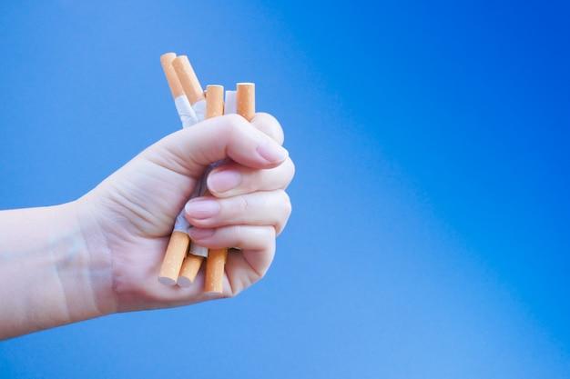 Zerbrochene zigarette zur hand. mit süchtig machenden nikotinproblemen gewinnen. rauchen verboten. verlassen des suchtkonzepts.