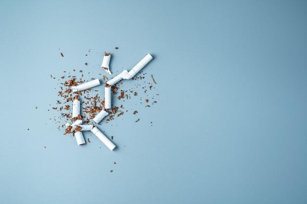 Zerbrochene zigaretten unter dem verstreuten tabak auf einem blauen hintergrund.