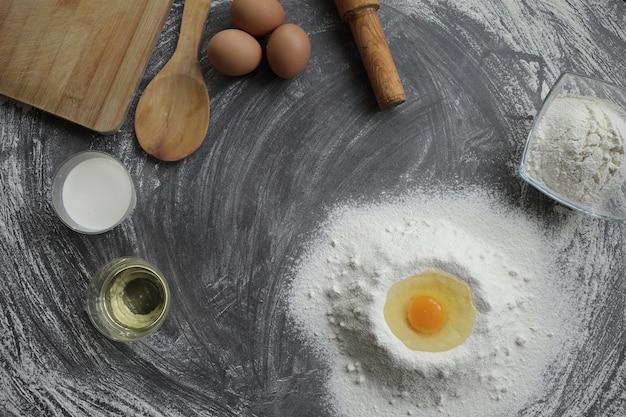 Zerbrochenes hühnerei in einem mehlhaufen neben anderen produkten und werkzeugen zur herstellung von kuchen oder brot auf einem grauen tisch