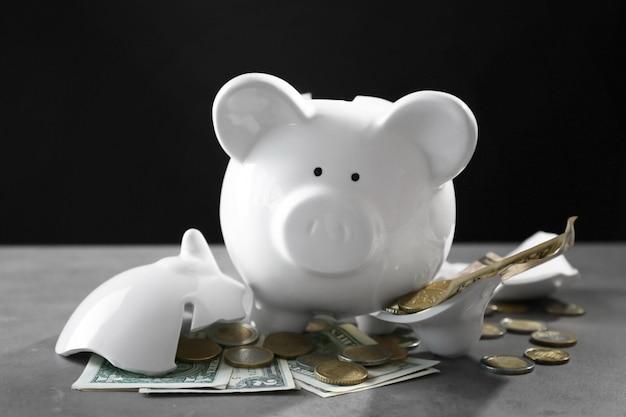 Zerbrochenes sparschwein mit geld auf dem tisch