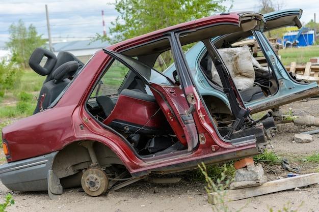 Zerbrochenes, zerknittertes, verbeultes auto nach dem unfall. verlassene autowracks. müllkippe von autowracks. auto kaputt nach einem unfall.