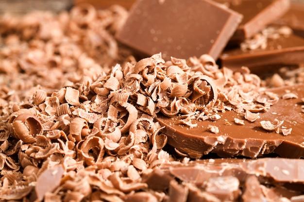 Zerbröckeln sie große und kleine stücke süßer milchschokolade, während sie desserts und nahaufnahmen von süßigkeiten auf einem holztisch zubereiten