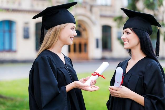 Zeremonie besprechen. zwei glückliche junge frauen in abschlusskleidern, die diplome halten und sprechen