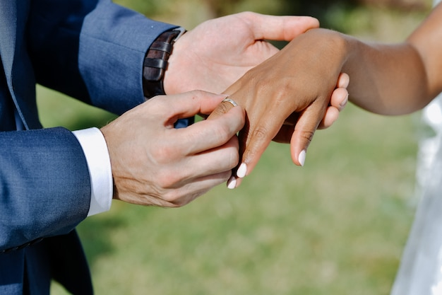 Zeremonie des aufbringens des eherings auf den finger der braut im freien