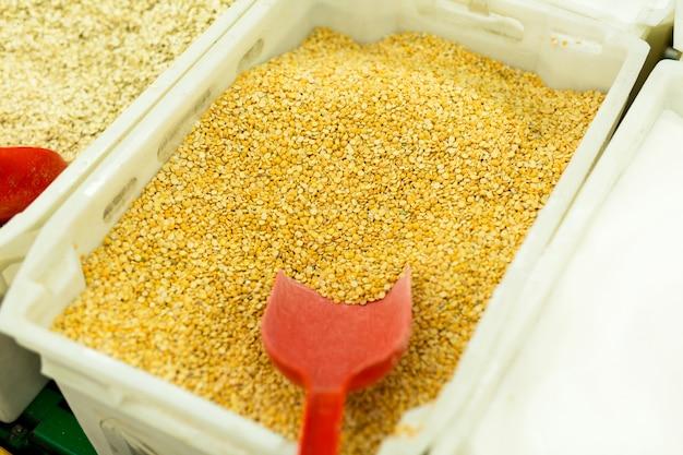 Zerkleinerte gelbe erbsen in kisten auf der theke im supermarkt. müsli im laden kaufen.
