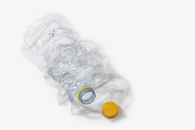 Zerkleinerte plastikflasche lokalisiert auf weiß. recycling-konzept. speicherplatz kopieren
