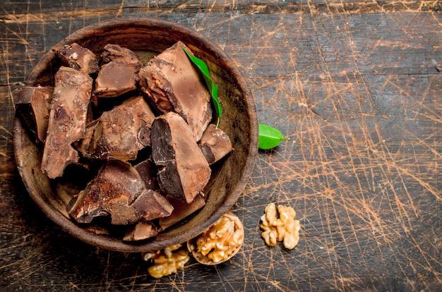 Zerkleinerte schokolade in der schüssel. auf einem hölzernen hintergrund.