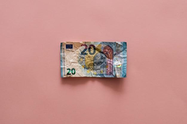 Zerknitterte 20-euro-rechnung über einem rosa tisch. geld sparen konzept