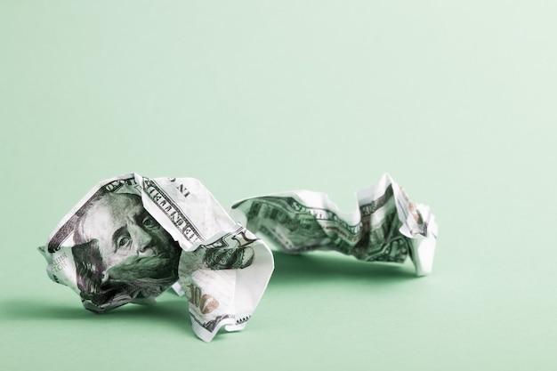 Zerknitterte dollarnoten auf grünem hintergrund