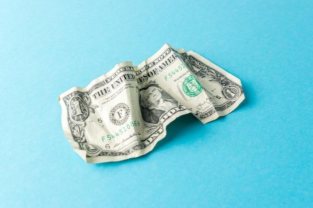 Zerknitterte ein dollarschein auf blauem hintergrund