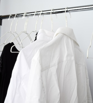 Zerknitterte hemden des weißen mannes, die an einem metallaufhänger hängen