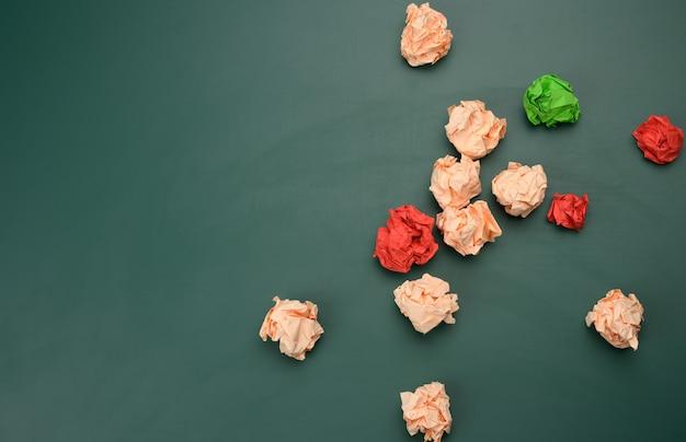 Zerknitterte papierbälle auf einer grünen oberfläche, ansicht von oben. konzept der suche nach innovativen ideen, richtigen lösungen. beseitigung von fehlern, vereinheitlichung um eine idee, draufsicht
