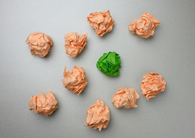 Zerknitterte papierbälle auf grauer oberfläche, ansicht von oben. das konzept, innovative ideen, die richtigen lösungen zu finden. beseitigung von fehlern, vereinheitlichung um eine idee