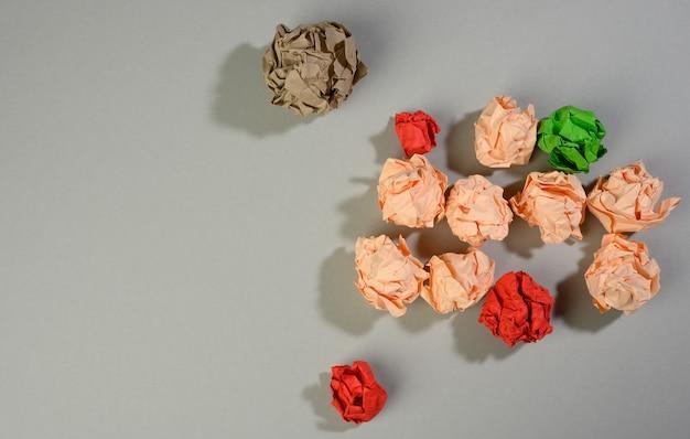 Zerknitterte papierbälle auf grauer oberfläche, ansicht von oben. konzept der suche nach innovativen ideen, richtigen lösungen. beseitigung von fehlern, vereinheitlichung um eine idee, draufsicht