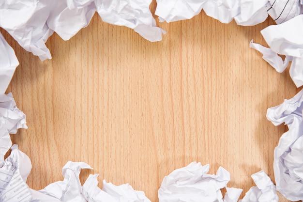Zerknitterte papierbälle auf hölzernem hintergrund.