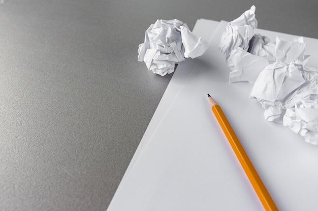 Zerknitterte papierbälle und ein bleistift mit leerem papierkacke