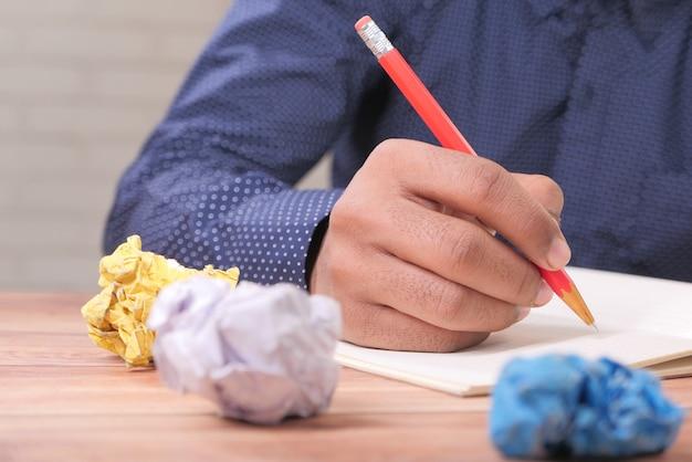 Zerknitterte papierkugel und person, die auf notizblock auf holztisch schreibt