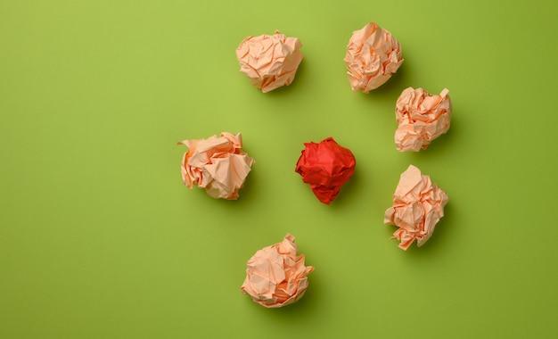 Zerknitterte papierkugeln auf einer grünen oberfläche, draufsicht. das konzept, innovative ideen zu finden, die richtigen lösungen. beseitigung von fehlern