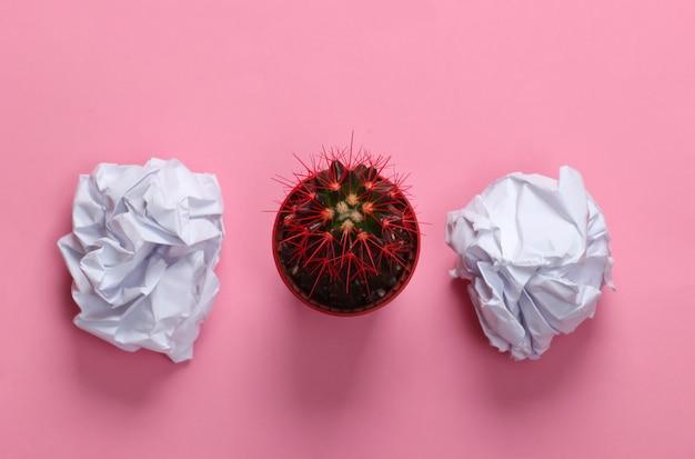 Zerknitterte papierkugeln, kaktustopf auf rosa pastell