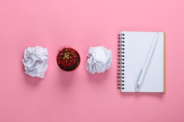 Zerknitterte papierkugeln, kaktustopf und notizblock auf rosa pastell. arbeitsplatz
