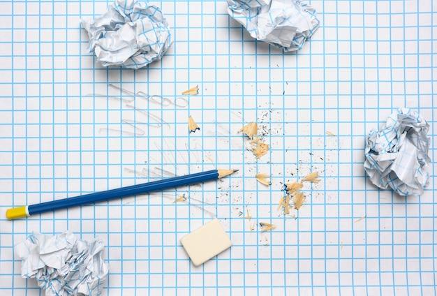 Zerknitterte papierkugeln und ein angespitzter holzstift mit spänen auf einem karierten papierblatt