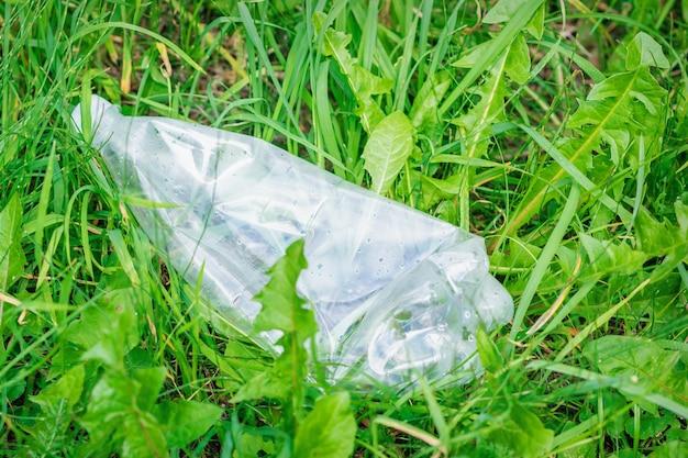Zerknitterte plastikflasche, die im grünen gras liegt. konzept des umweltschutzes
