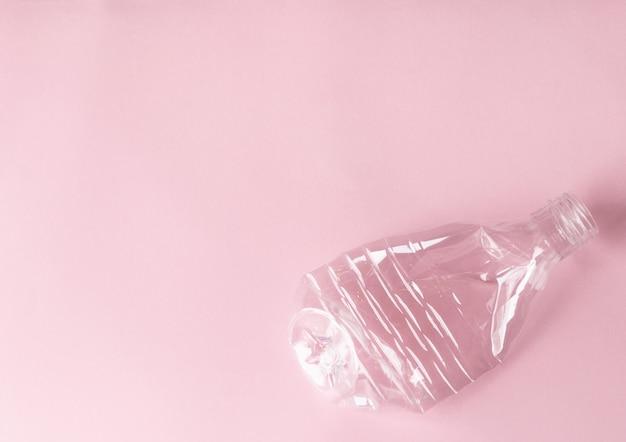 Zerknitterte plastikflasche für trinkwasser auf einem rosa. recycling, abfalltrennung, umweltschutz. ökologiethema.