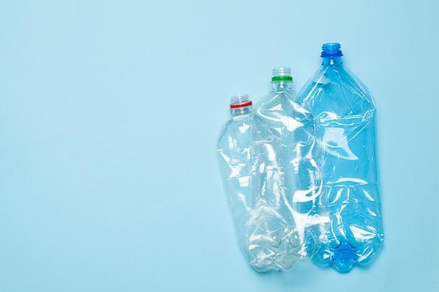 Zerknitterte plastikflaschen auf einem blau. plastikmüll. kopieren sie platz für text.