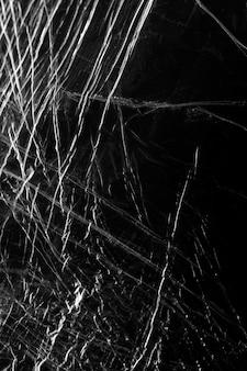 Zerknitterte plastikfolie textur auf einem schwarzen hintergrundbild