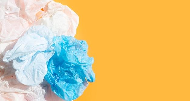 Zerknitterte plastiktüten auf orangefarbener oberfläche