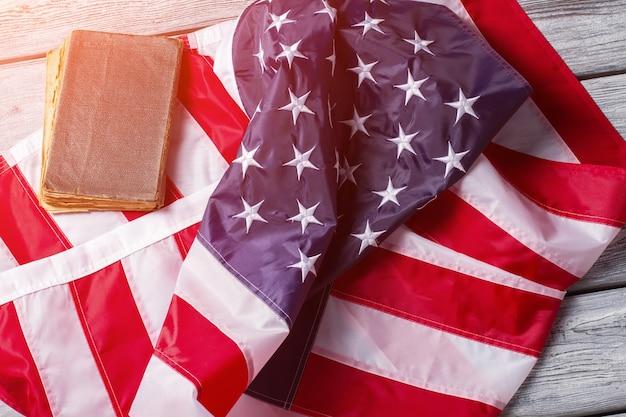 Zerknitterte usa-flagge und buch. banner und buch unter sonnenlicht. gehorcht dem gesetz. menschenrechte vor allem.