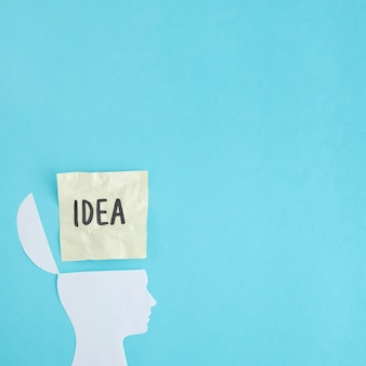 Zerknitterter Ideentext über dem weißen offenen Kopf auf blauem Hintergrund