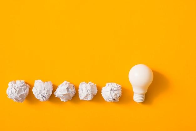 Zerknitterter papierball mit weißer glühlampe auf gelbem hintergrund