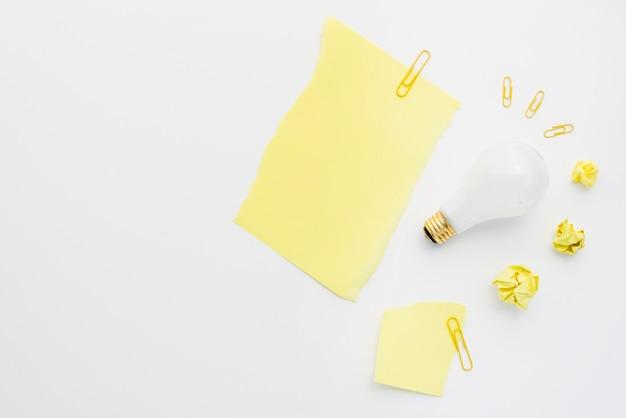Zerknitterter papierball mit weißer glühlampe und papierklammer auf weißem hintergrund