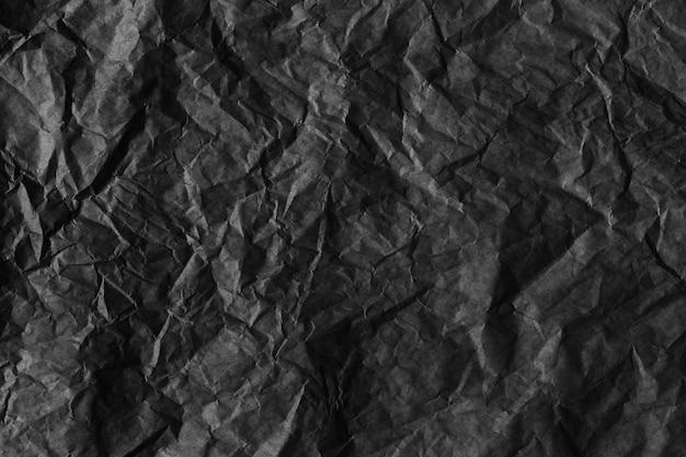 Zerknitterter texturhintergrund aus schwarzem papier für das design in ihrem arbeitskonzept.