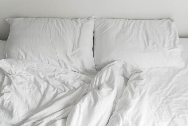 Zerknittertes bett mit weißer, unordentlicher kissendekoration im schlafzimmer