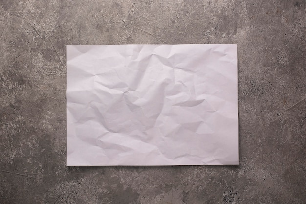 Zerknittertes blatt papier auf einer betonwand.
