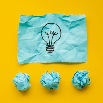 Zerknittertes blaues papier mit glühlampe in der markierung