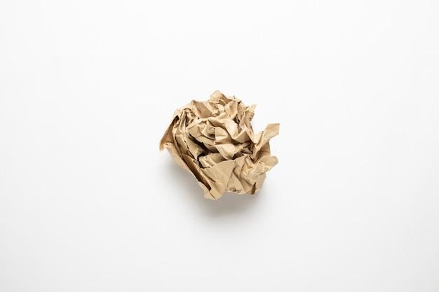 Zerknittertes braunes bastelpapier auf weißem hintergrund.