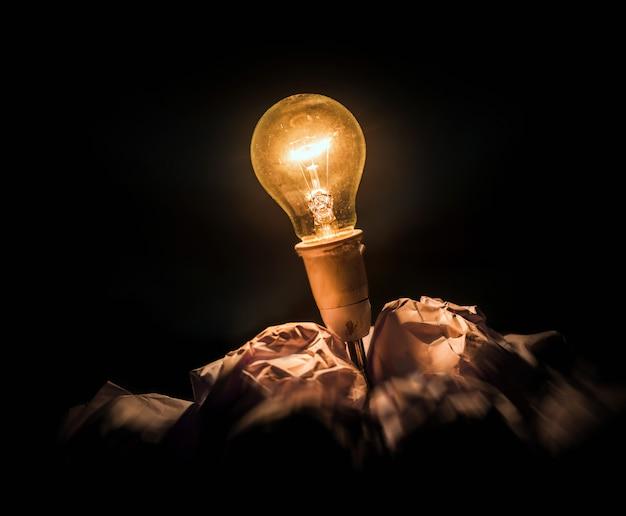 Zerknittertes büropapier und glühlampe
