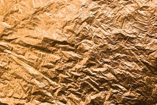 Zerknittertes gelbes farbiges papier. gold strukturierter hintergrund.