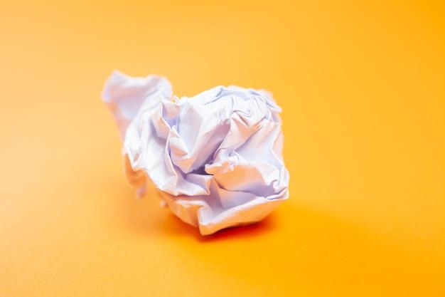 Zerknittertes papier auf oranger oberfläche