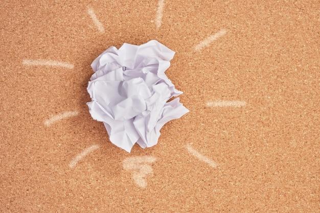 Zerknittertes papier in der form einer glühbirne auf einem korkbretthintergrund, planetenverschmutzungskonzept