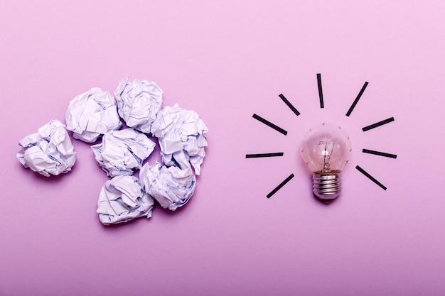 Zerknittertes papier und glühlampe auf purpur