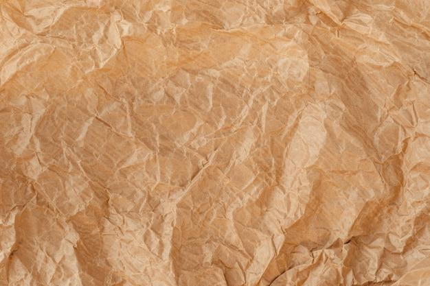 Zerknittertes wickelblatt, grunge-texturprobe recyceln. nahaufnahme der pergamentleinwand. geschenkpapier. kraftpapier textur. braune zerknitterte oberfläche.